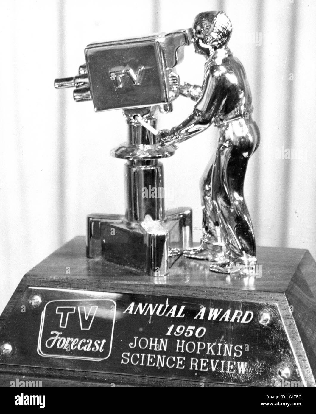 TV Forecast Award trophy with a statue of a man videotaping on top of a wooden base, the wooden base has a plaque that has engraved on it 'Annual Award 1950 John Hopkins Science Review, 1950. - Stock Image