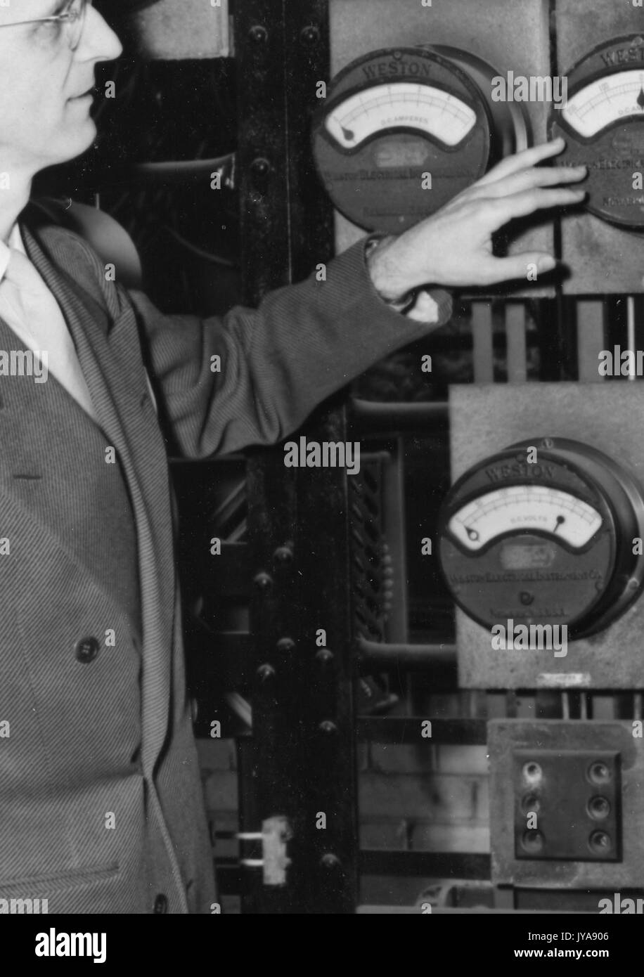American television host Lynn Poole on set of the Johns Hopkins Science review television program looking at an analog gauge, 1951. - Stock Image