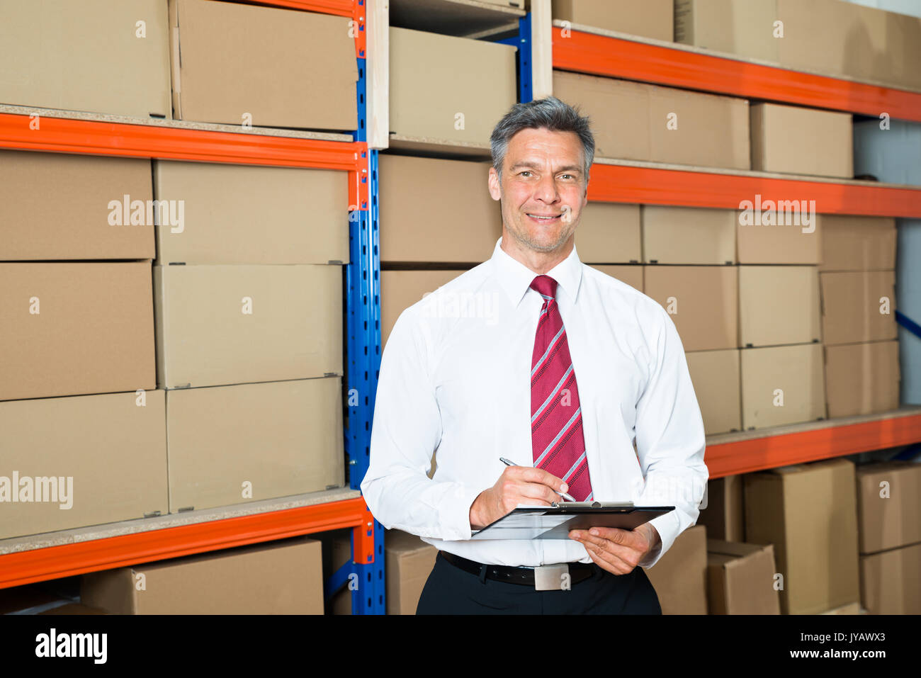 Happy Manager Writing On Clipboard In Distribution Warehouse - Stock Image