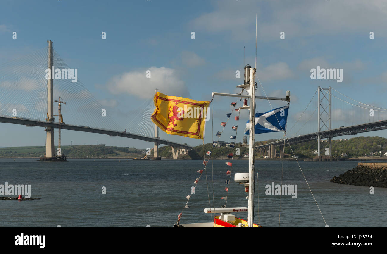 Scottish flags fly in front of iconic road bridges over Forth river, Scotland, UK Stock Photo