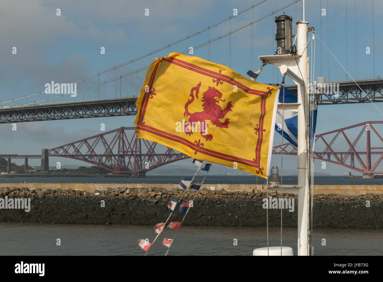 Scottish flags fly in front of iconic Scottish bridges, Firth of Forth, Scotland,  UK Stock Photo