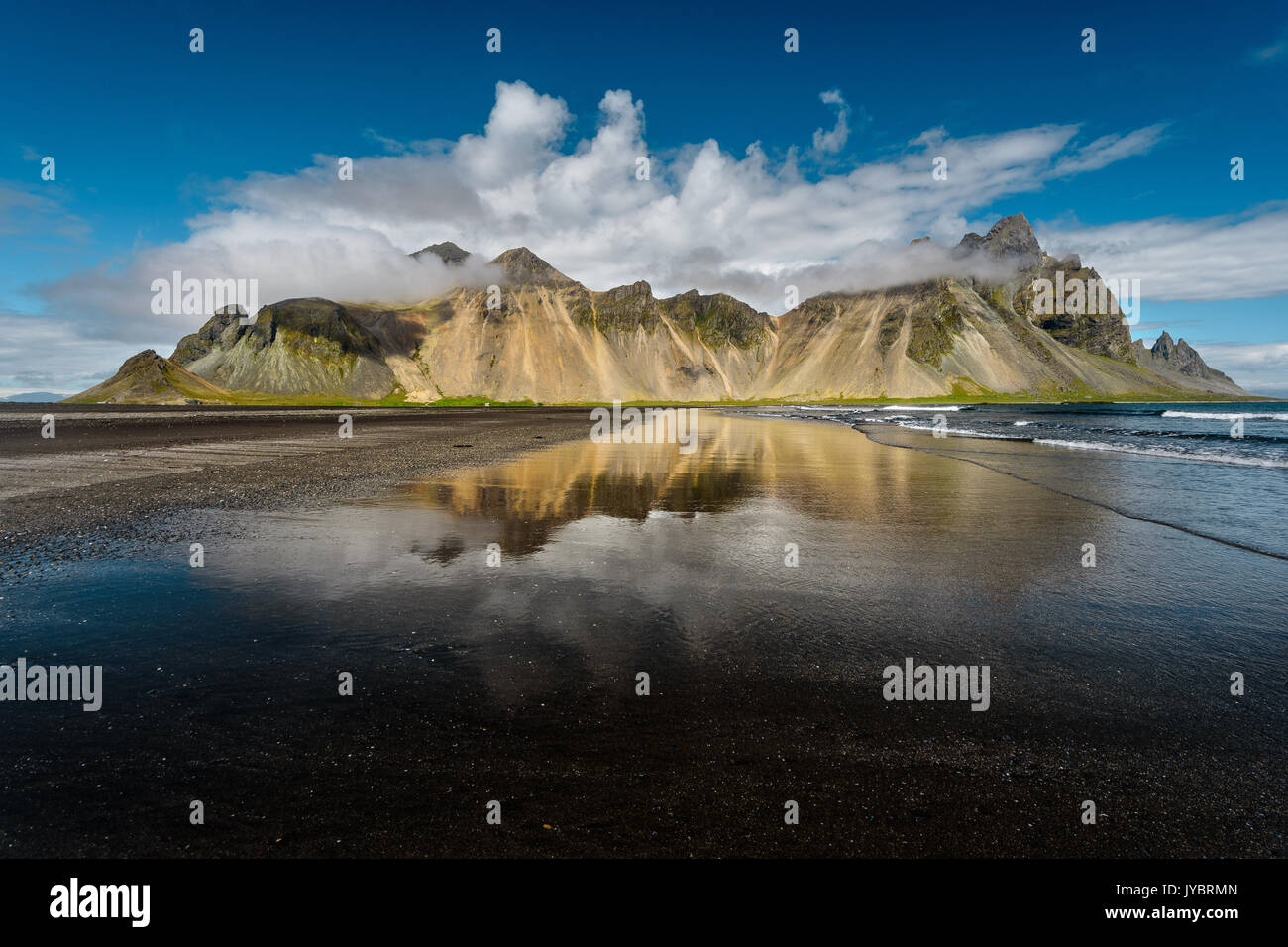 Vestrahorn reflections in the wet beach. Stock Photo