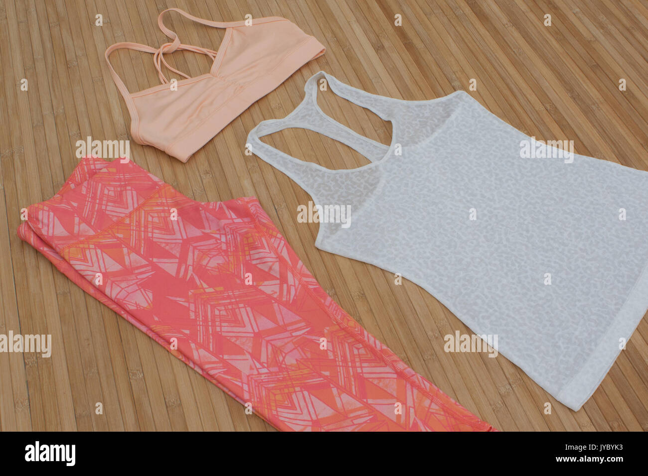 fitness, sportswear, yoga, leggings, capris, flatlay, bright, patterns, bamboo, workout, fashion, exercise, pink, coral, sports bra, tank top - Stock Image