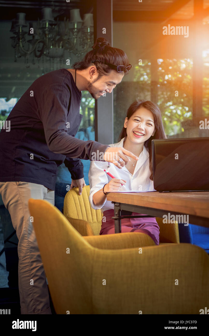 asian younger freelance man and  woman working with smiling face in home office - Stock Image