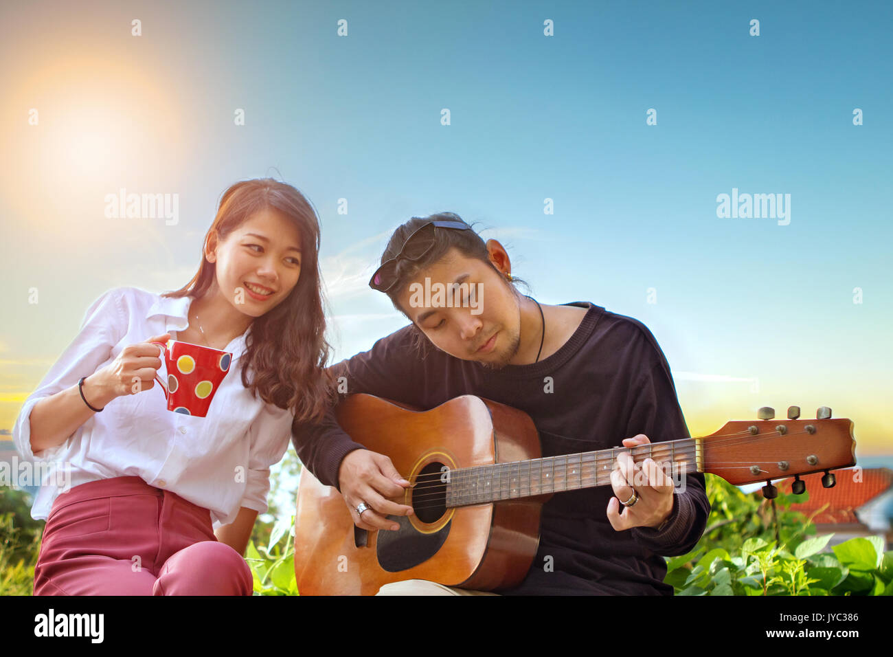 couples of younger asian man and woman relaxing playing guitar in park - Stock Image