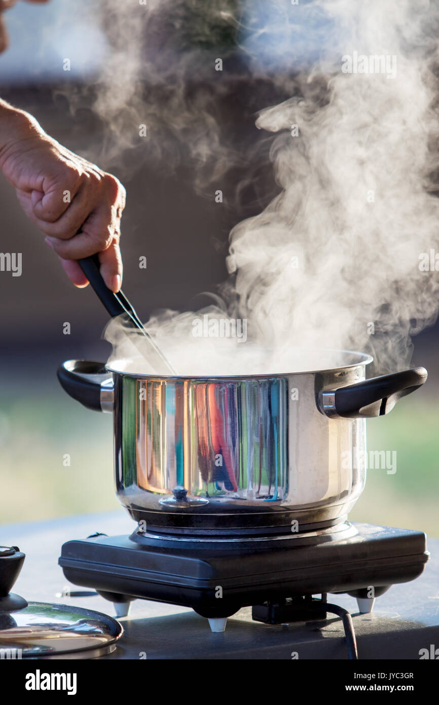 hand cooking on hot pot with water steam Stock Photo