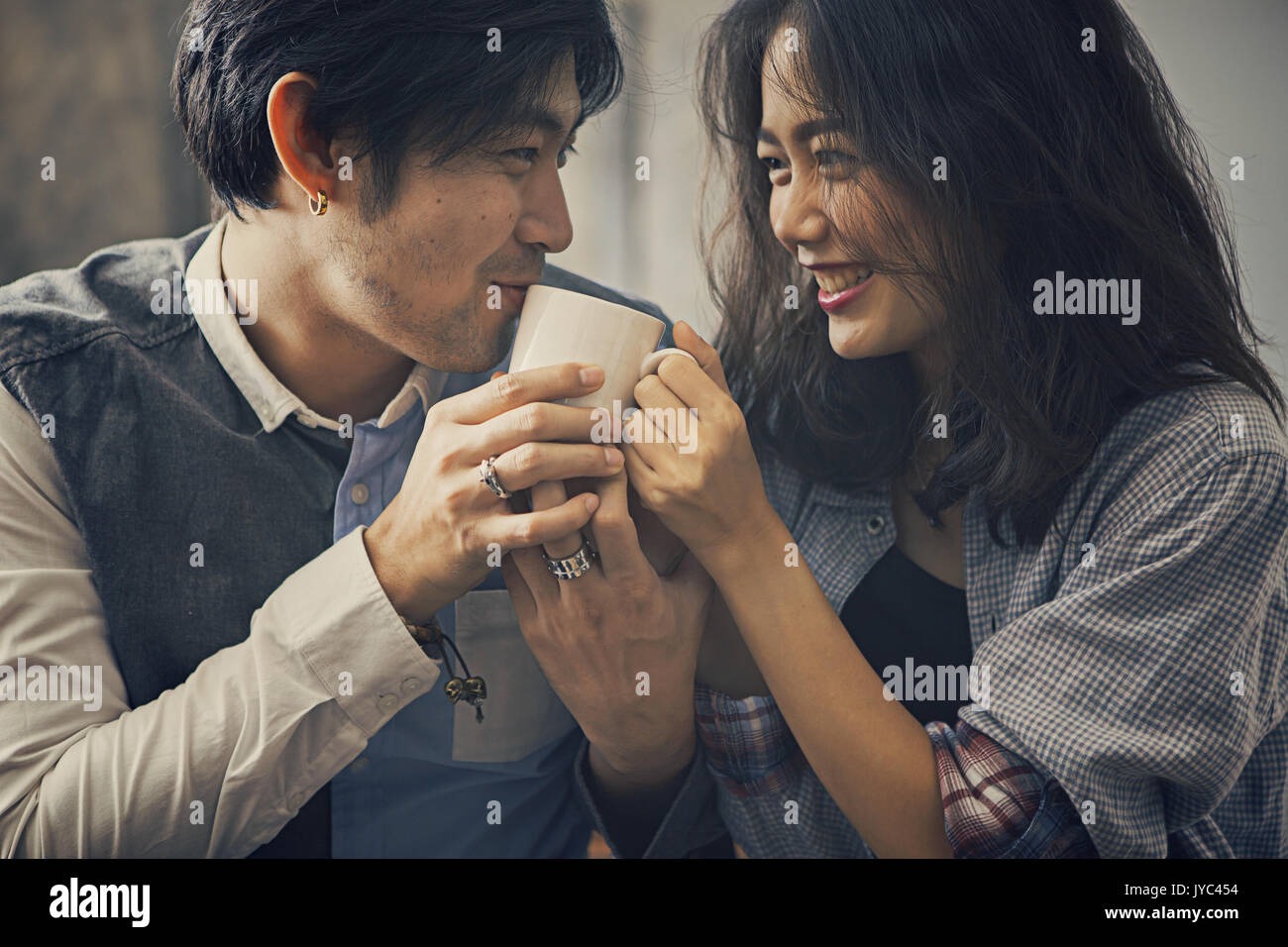 couples of asian younger man and woman happiness emotion with hot coffee cup in hand - Stock Image
