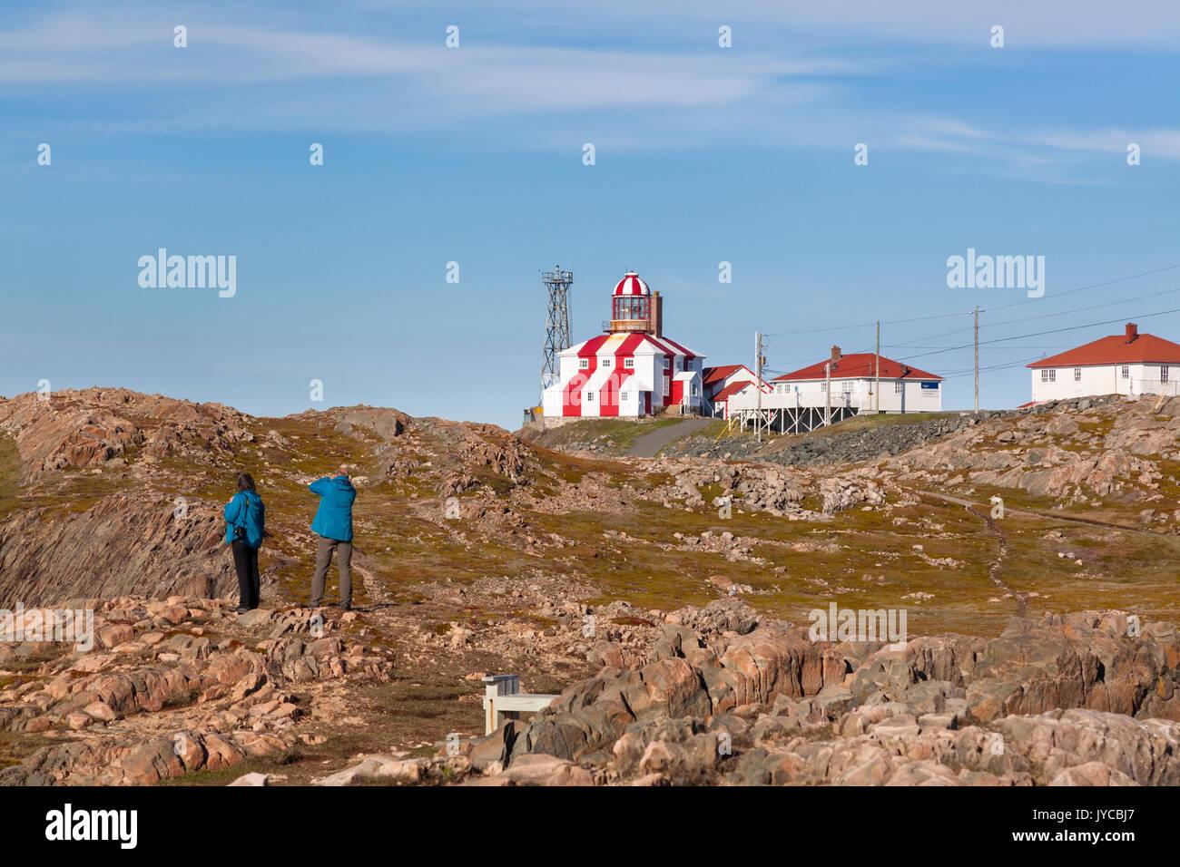 Tourists visiting the Cape Bonavista Lighthouse that is perched atop a rocky landscape in Bonavista,, Newfoundland and Labrador, Canada. - Stock Image