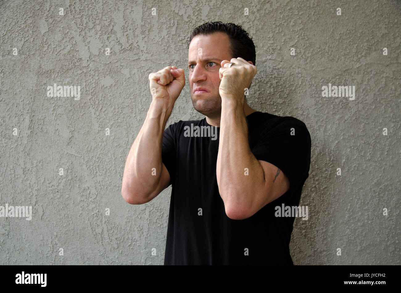 Furious man with clenched fists. - Stock Image