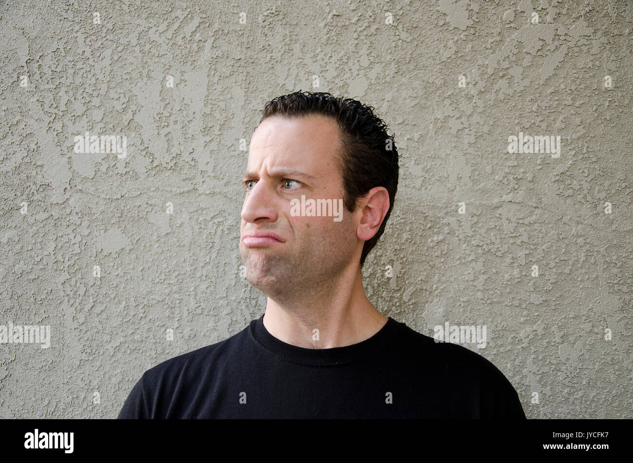 Man in front of a beige background making a disgruntled face looking to the left. - Stock Image