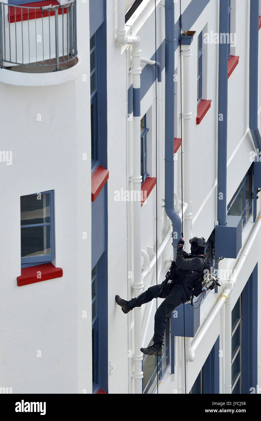 One unrecognizable Counter-terrorism police officer abseiling a building during an exercise. - Stock Image