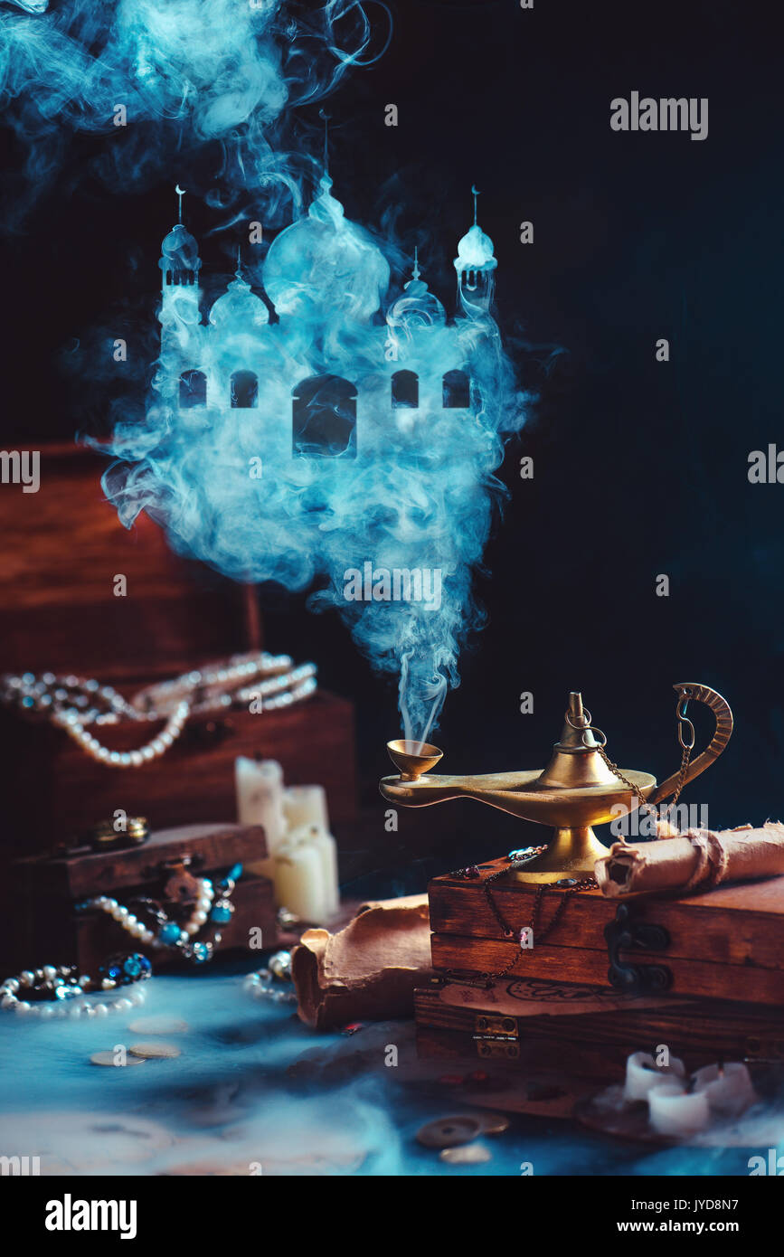 Dark dreamy still life with magic lamp and mystic smoke forming an arabic castle. Boxes filled with treasure and jewelry on a background. - Stock Image