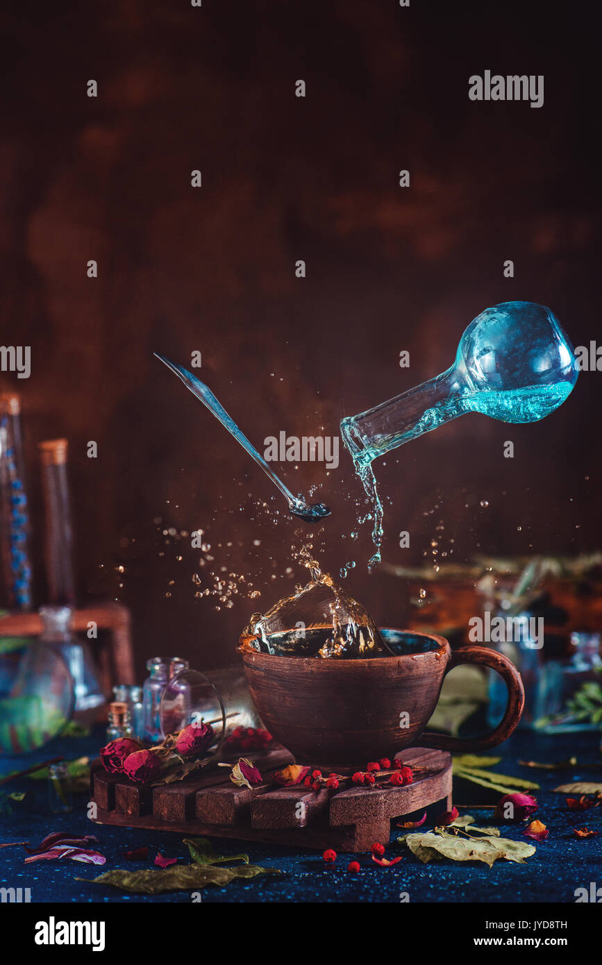 Flying potion bottle with pouring liquid in a magical still life. Brewing enchanted tea. Wooden background with magical supplies. Copy space. - Stock Image