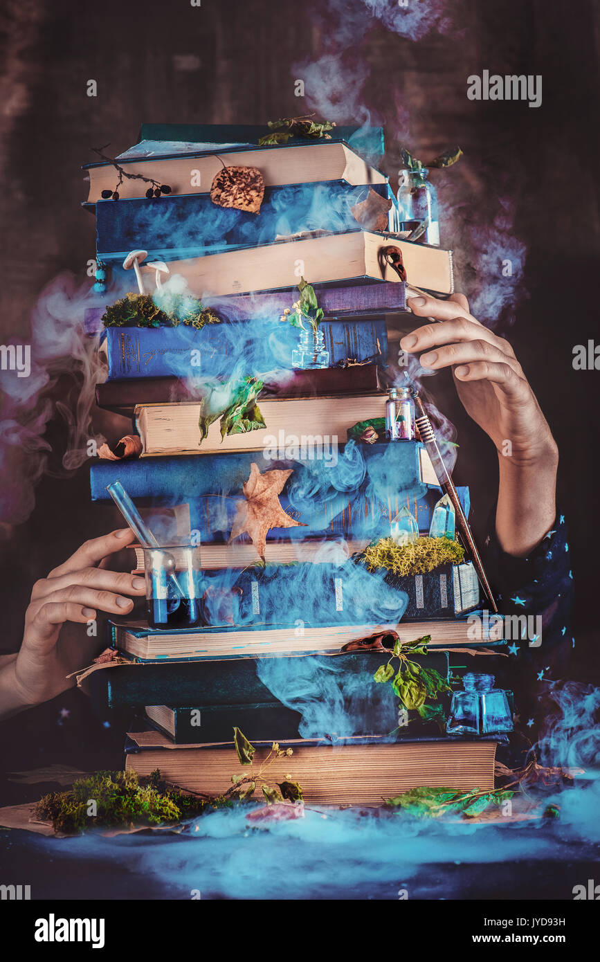A pile of magical books with wizard hands. - Stock Image