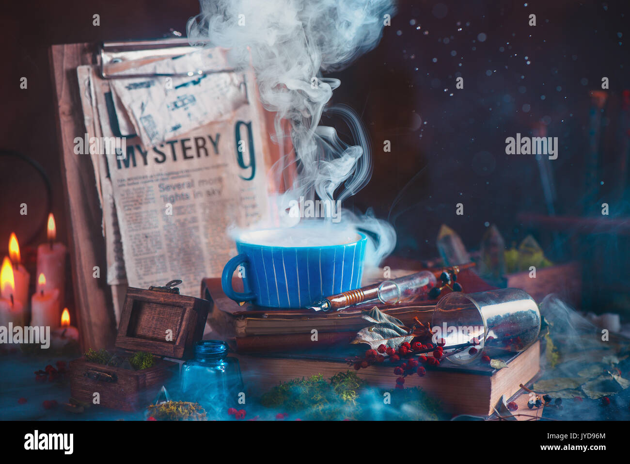 Rising steam in a ceramic tea cup on a wooden background with candles, mystery newspaper clips, books, leaves and Stock Photo
