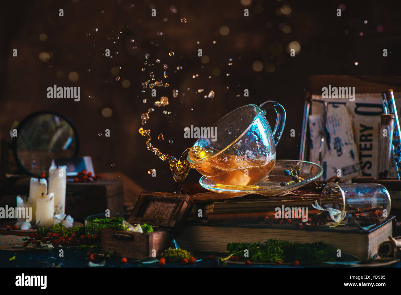 Tea splash in a glass cup on a wooden background with candles, mystery newspaper clips, books, leaves and moss. Action still life with tea drops bokeh - Stock Image