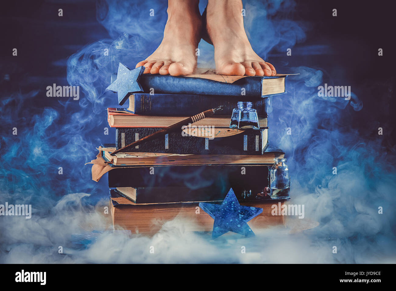 Kid standing on a pile of books in the middle of a cloud of smoke. Dark still life in shades of blue. Education metaphor. - Stock Image