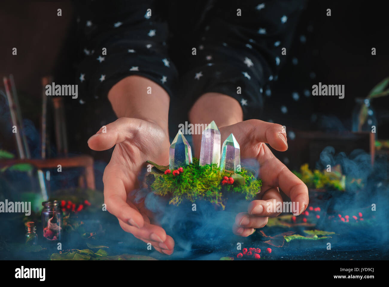 Young witch holding a floating turf with moss and crystals. Mystical scene with smoke and magical supplies. Star pattern sleeves of witch clothes. - Stock Image