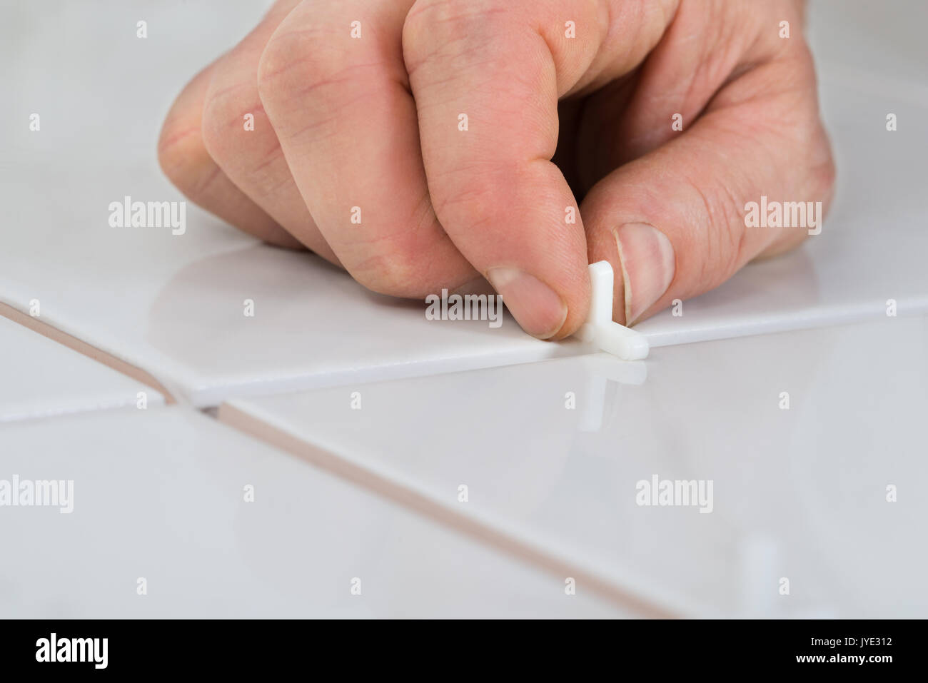 Close-up Of A Person's Hand Placing Spacers Between Ceramic Floor Tiles - Stock Image