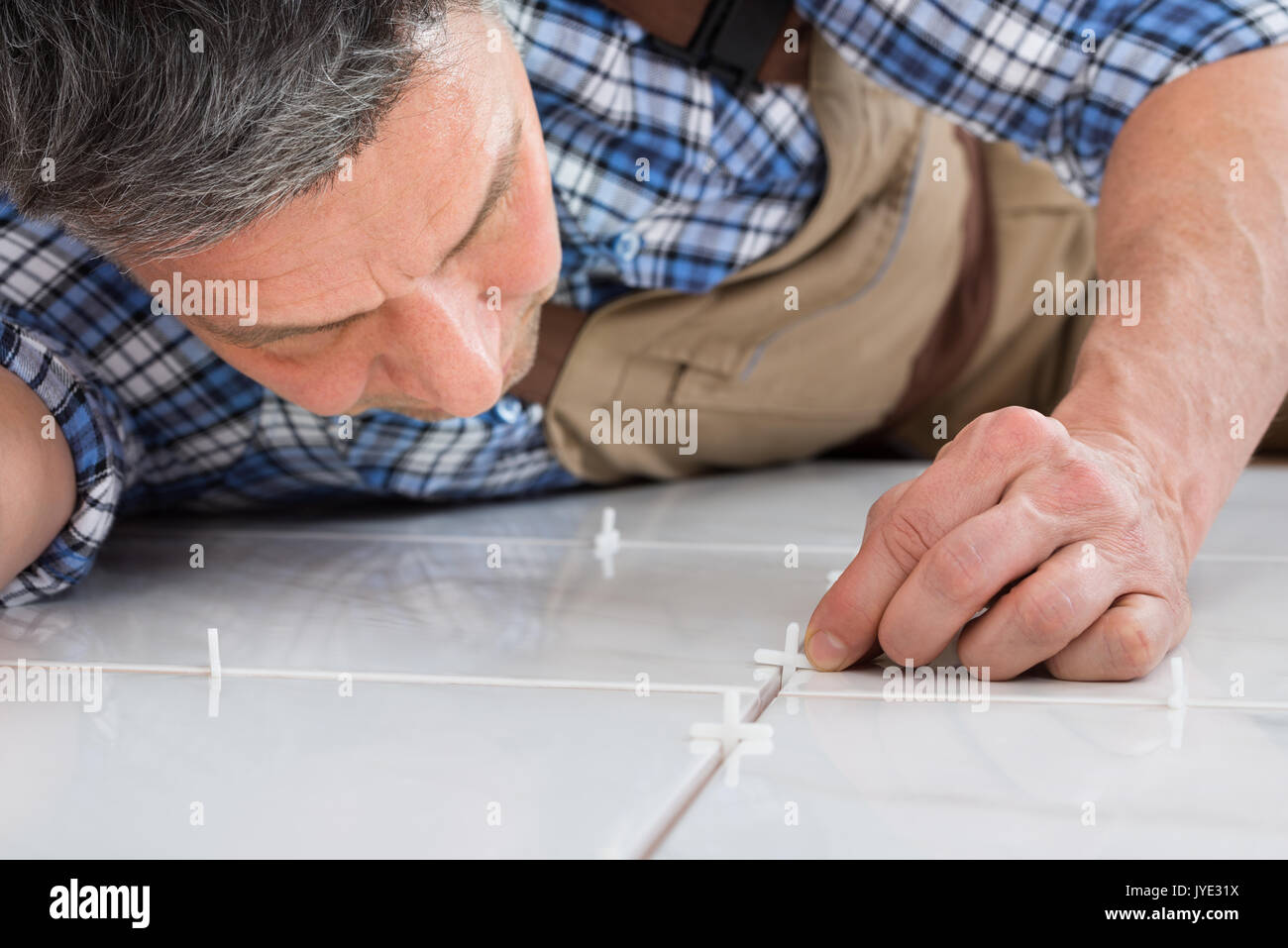 Close-up Of A Handyman Lying On Floor Placing Spacers Between Tiles - Stock Image