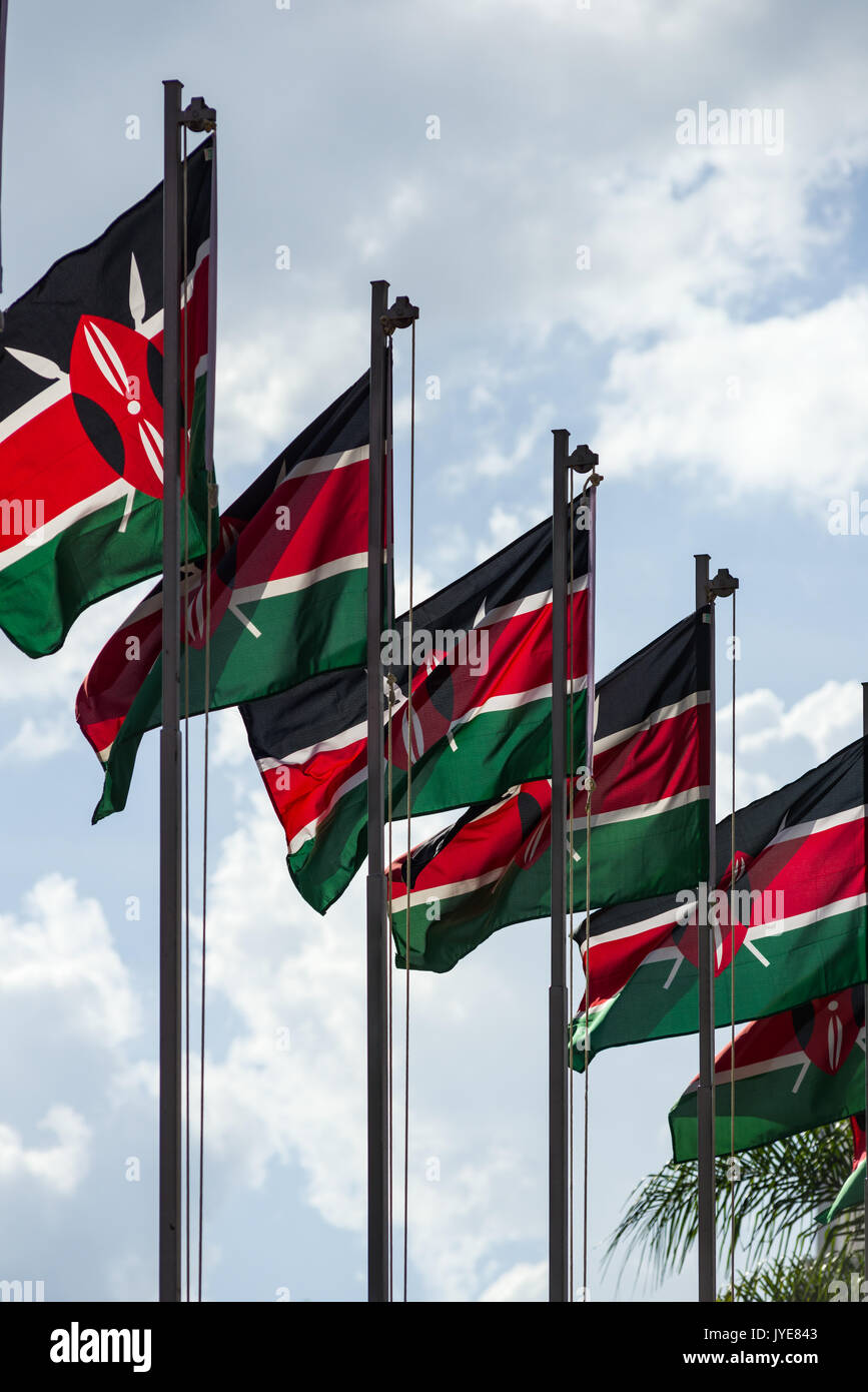 A row of Kenyan flags on poles waving in the wind on a sunny day, Nairobi, Kenya Stock Photo