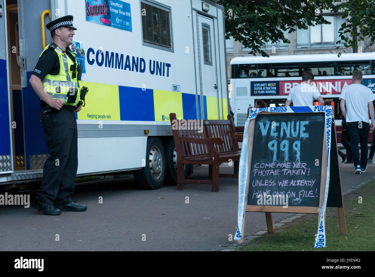 Police Scotland Command Unit stationed in Princes Street Gardens during Edinburgh Fringe Festival, nicknamed Venue 999 with policeman standing by van - Stock Image