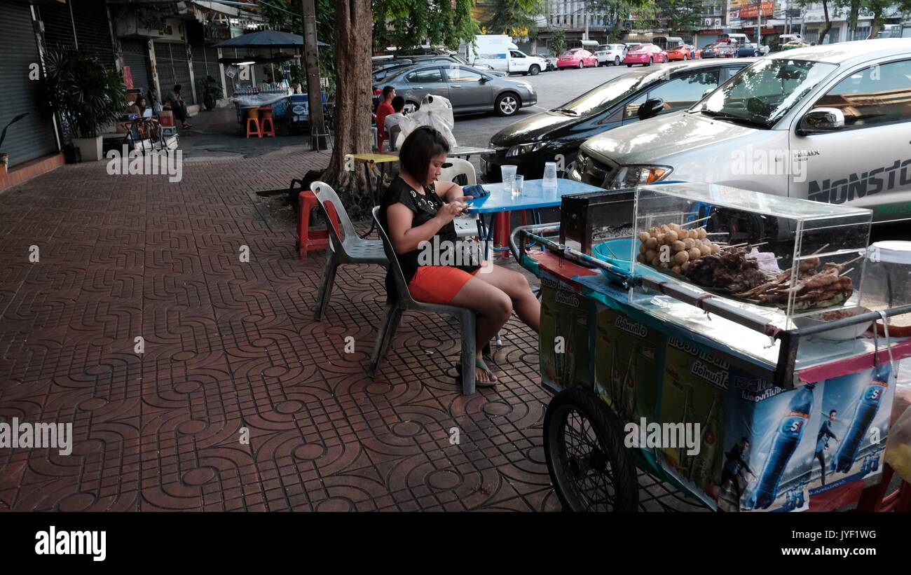 Vendor Lady Sitting at Wong Wian Yi Sip Song Karakada Khom Road Chinatown Samphanthawong Bangkok Thailand - Stock Image