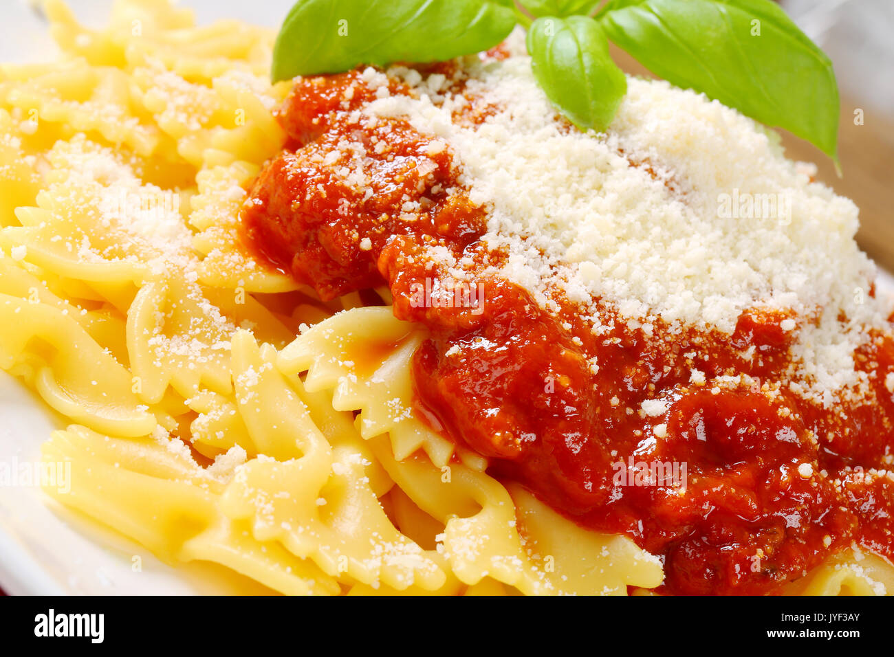 Bow-tie pasta with thick tomato sauce and parmesan - Stock Image