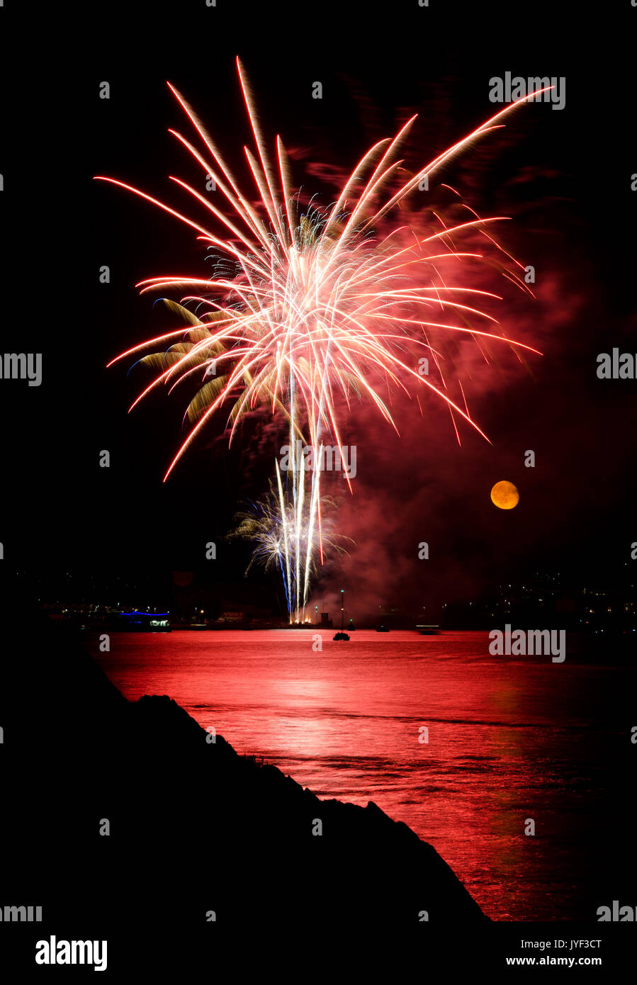 PLYMOUTH, ENGLAND. 10th August 2017. The moon rises during the British Firework Championships, a huge firework competition held annually in Plymouth. - Stock Image