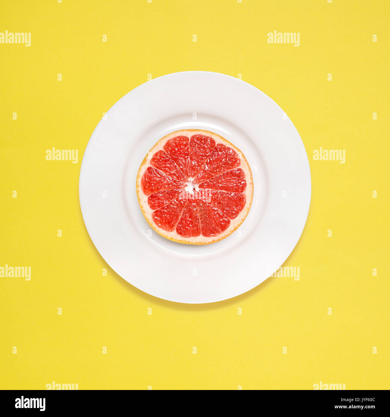 Creative photo of a grapefruit slice on white plate on yellow background. - Stock Image