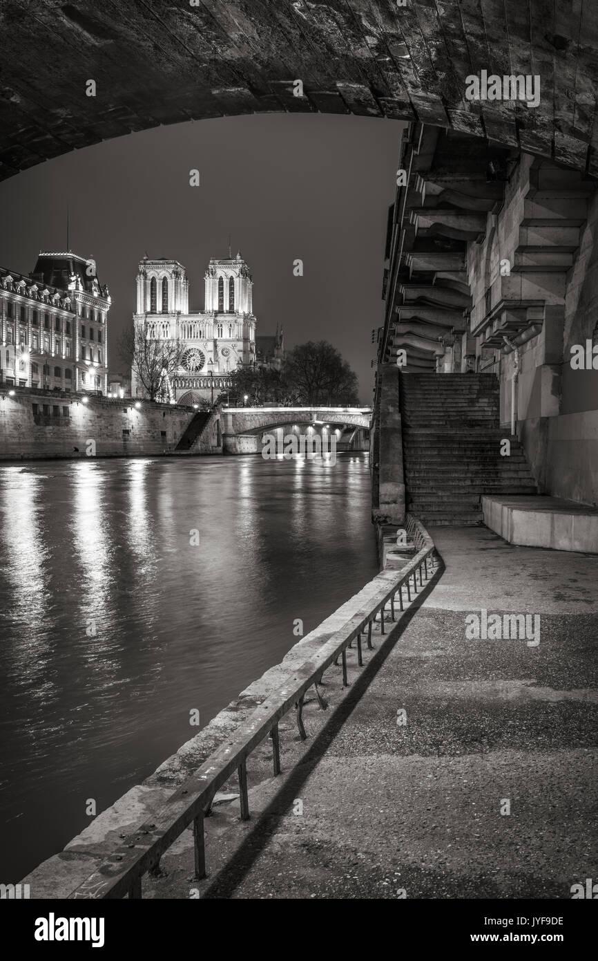 Notre Dame de Paris cathedral from the Seine River banks at night in Black & White. Ile de la Cite, Paris, France - Stock Image