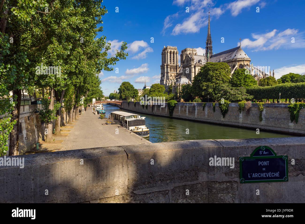 Notre Dame de Paris cathedral on Ile de La Cite with the Seine River in summer. Pont de l'Archeveche, Paris, France - Stock Image
