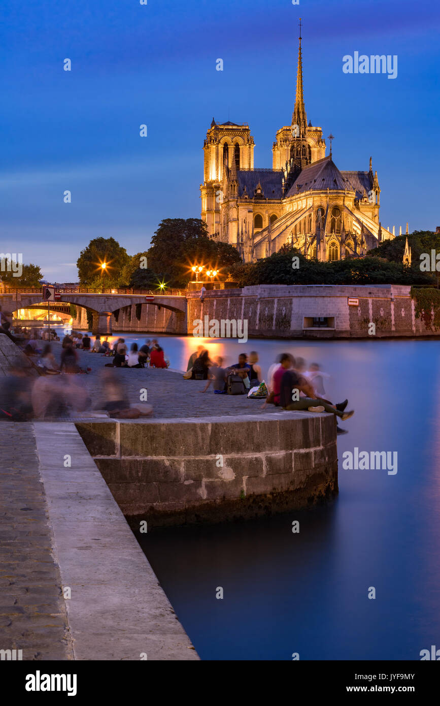 Evening on the Seine River banks in Summer with view of Notre Dame de Paris cathedral - Stock Image