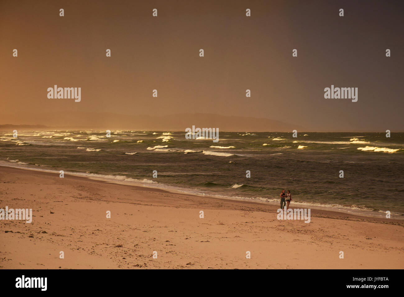 Couple on the Seven Mile Beach with Sea, New South Wales, Australia - Stock Image
