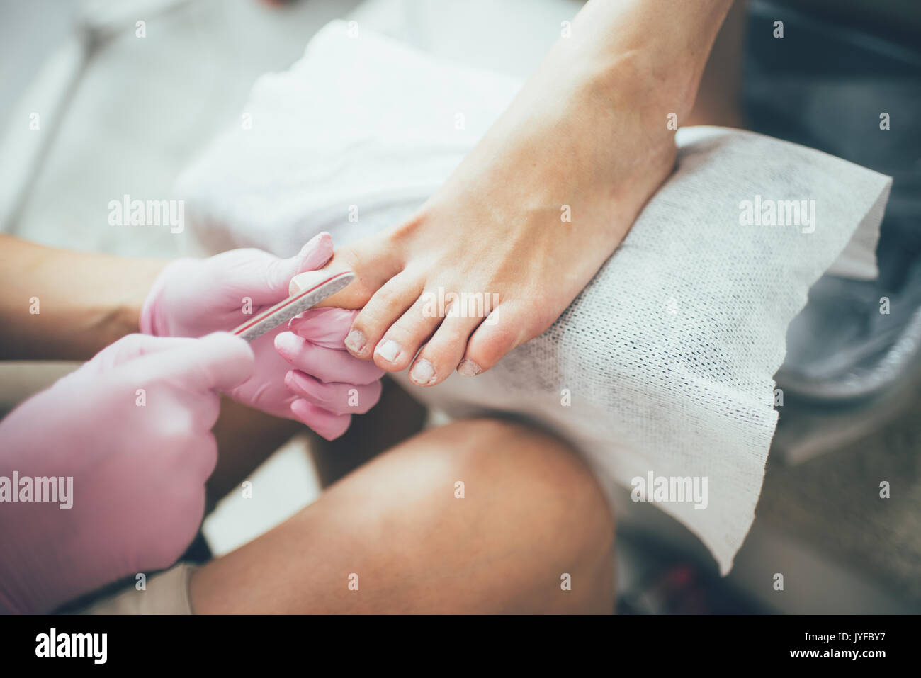 hands making a pedicure. Beauty salon, female feet, real picture - Stock Image