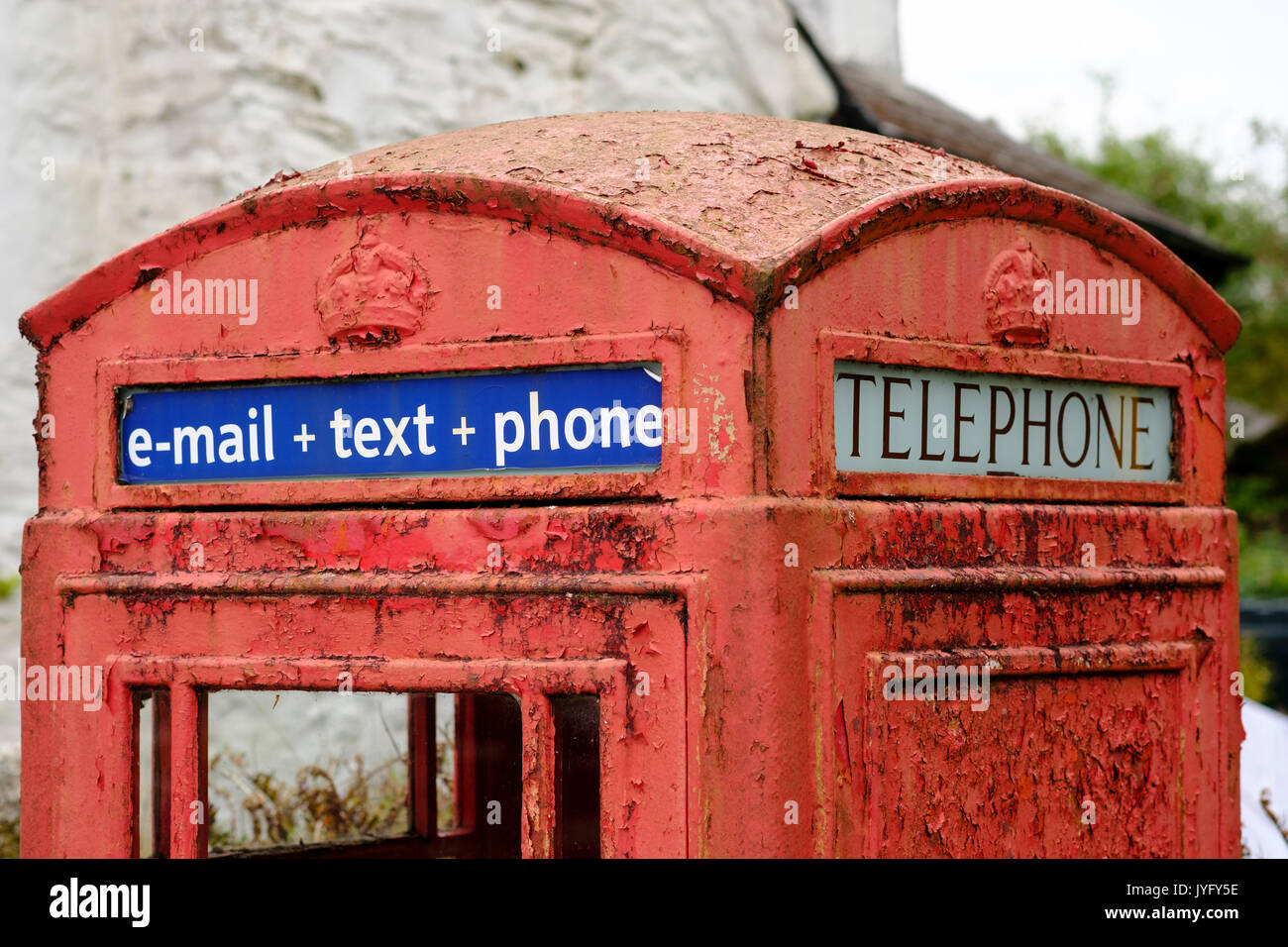 Old red telephone cell with writing e-mail + text + phone, St Neot, Bodmin Moor, Cornwall, England, United Kingdom - Stock Image