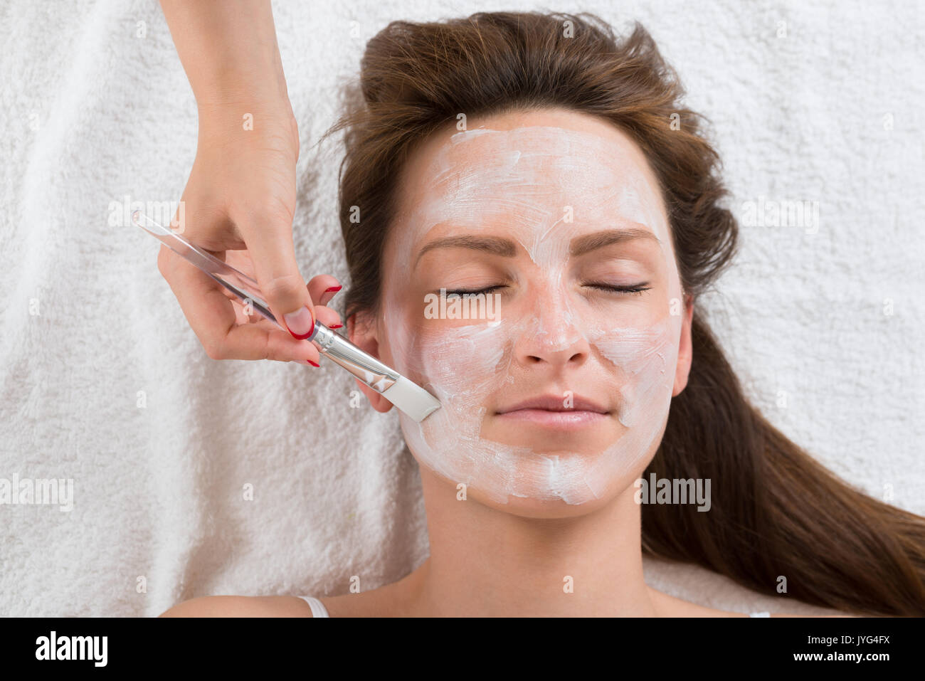 Therapist Hands With Brush Applying Face Mask To A Young Woman In A Spa - Stock Image