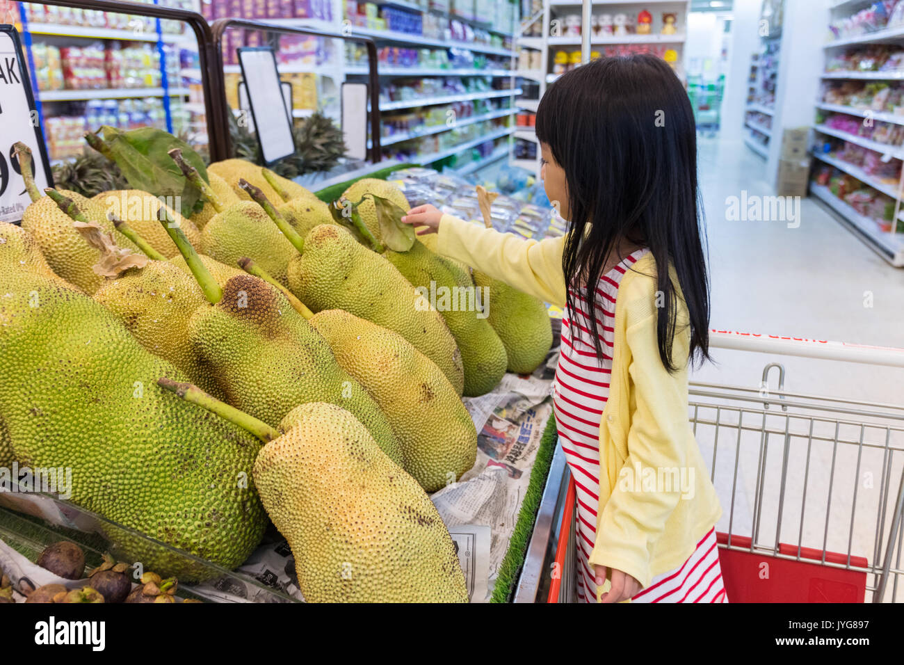 Asian Little Chinese Girl choosing fruits in supermarket - Stock Image