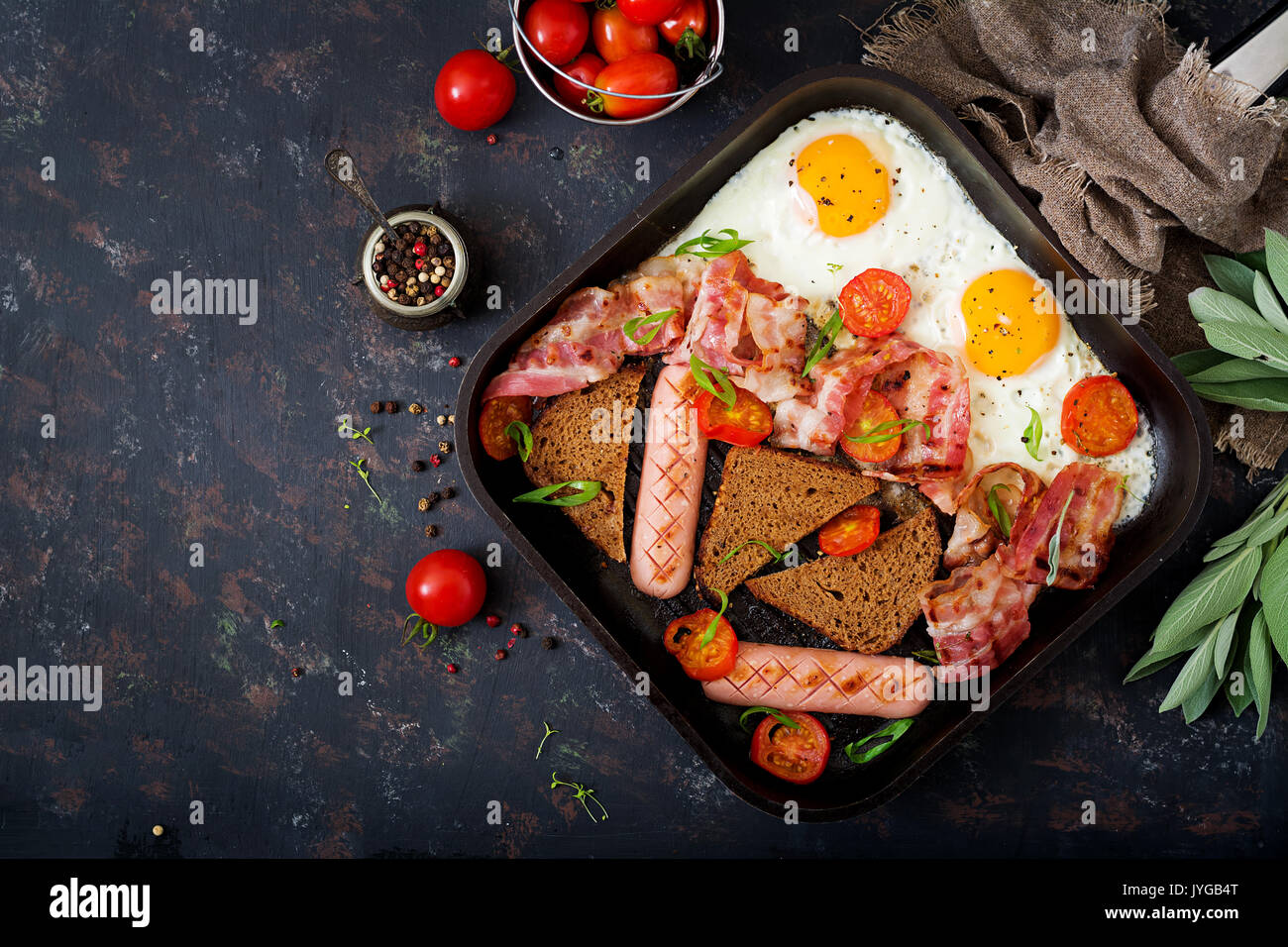 English breakfast - fried egg, sausage, tomatoes, bacon and toast. Top view. Flat lay - Stock Image