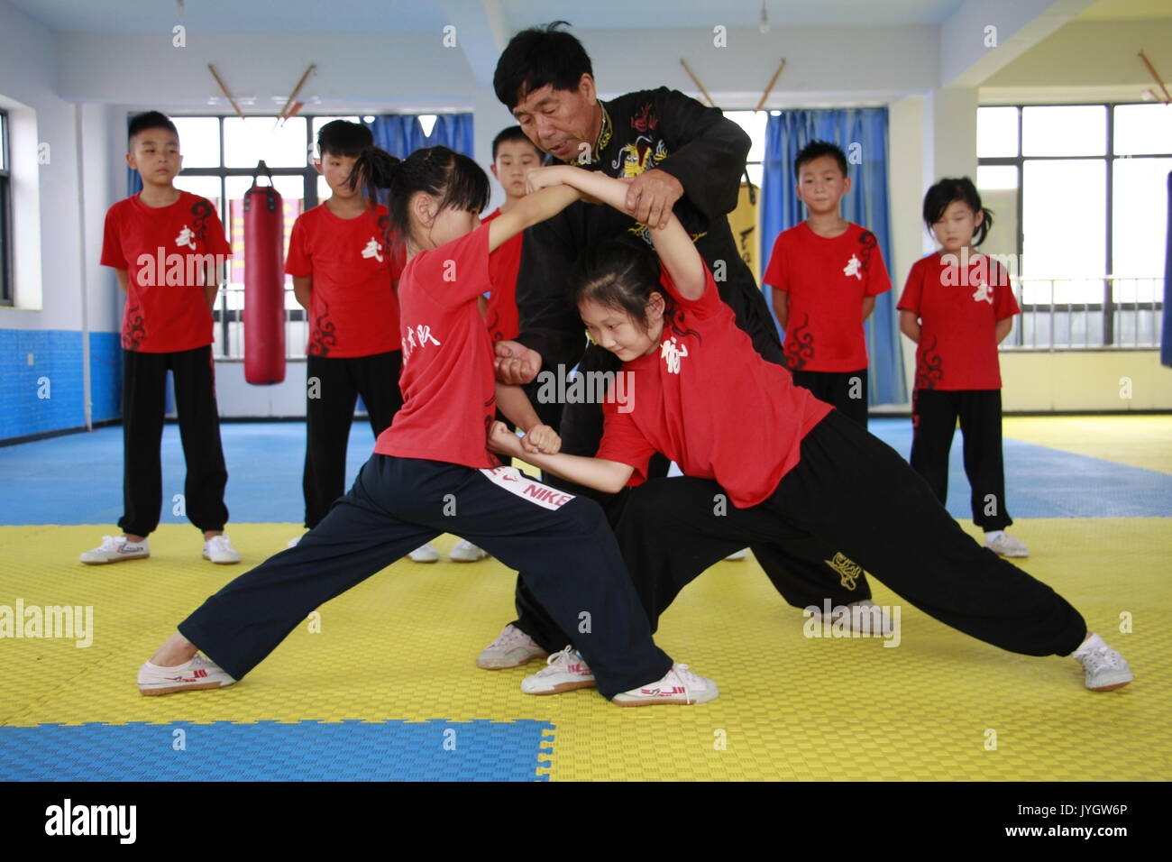 Handan. 19th Aug, 2017. Pupils learn Wushu from intangible cultural heritage inheritor Wang Shaoting in Cheng'an County in north China's Hebei Province, Aug. 19, 2017. Various extracurricular activities attracted many young students in China in the summer vacation time. Credit: Wang Junyong/Xinhua/Alamy Live News - Stock Image
