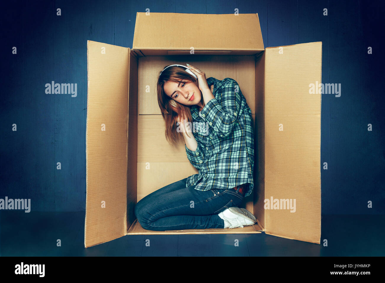 Introvert concept. Woman sitting inside box and with headphones - Stock Image