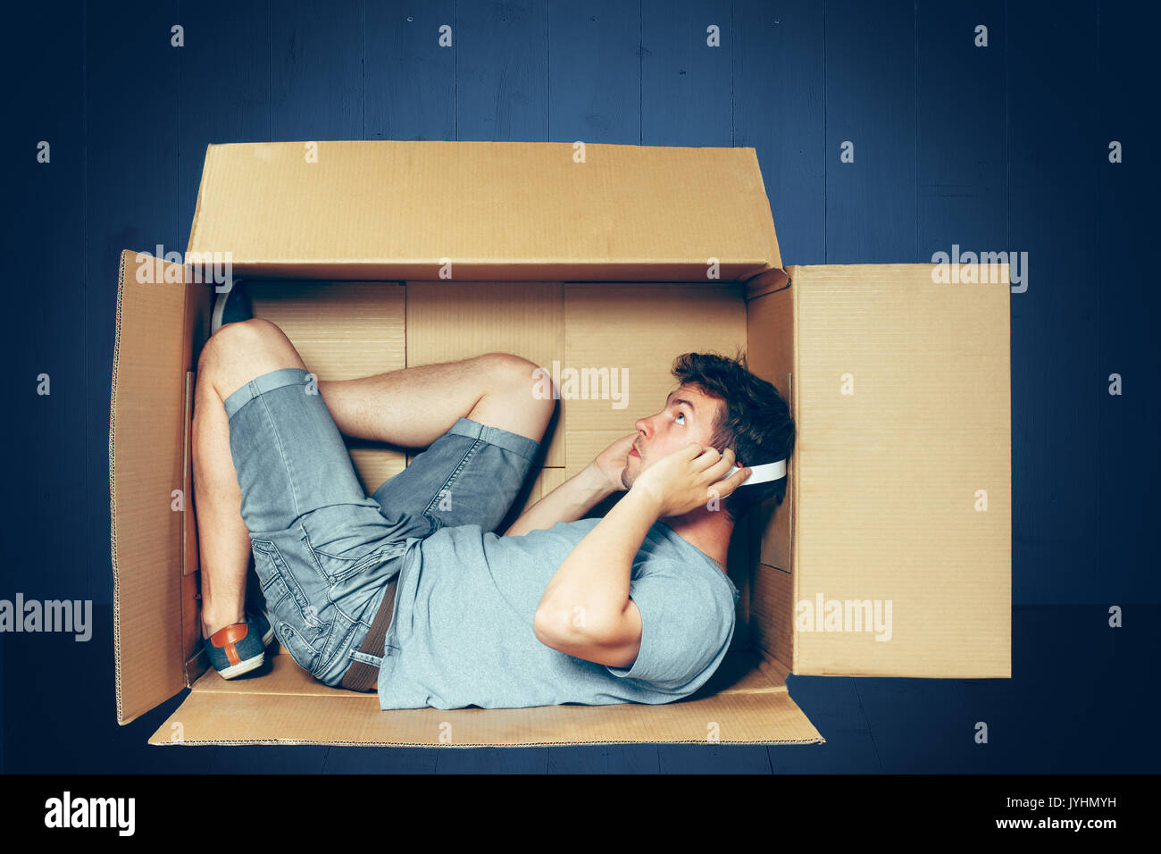 Introvert concept. The man sitting inside box with headphones - Stock Image