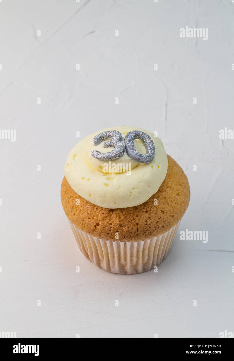 Single vanilla sponge cup cake with silver glitter number 30 on top of creamy white frosting isolated on rustic white background - celebration backgro - Stock Image