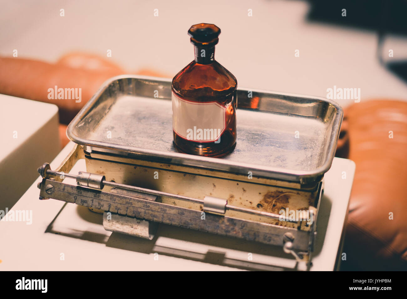 old empty medicine bottle on scale - vintage look - Stock Image
