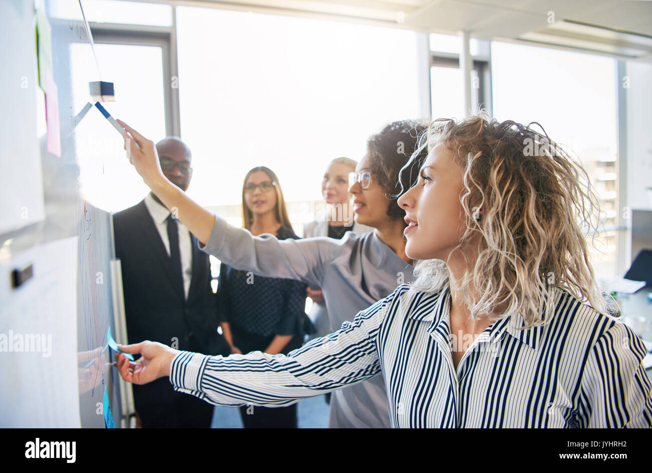 Group of focused business colleagues brainstorming together on a whiteboard during a strategy session in a bright - Stock Image