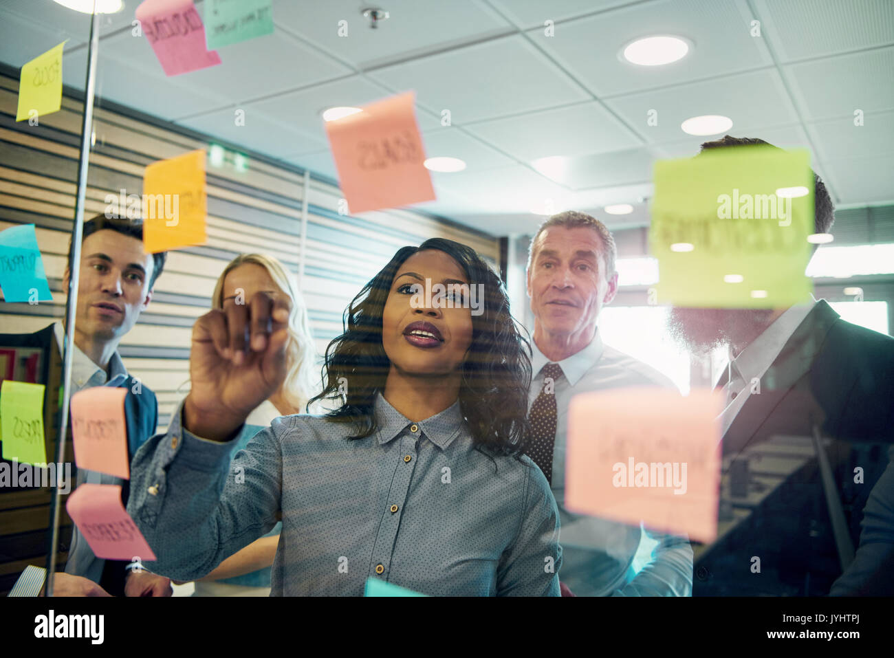Group of businesspeople brainstorming with woman in foreground, putting sticky note on glass - Stock Image
