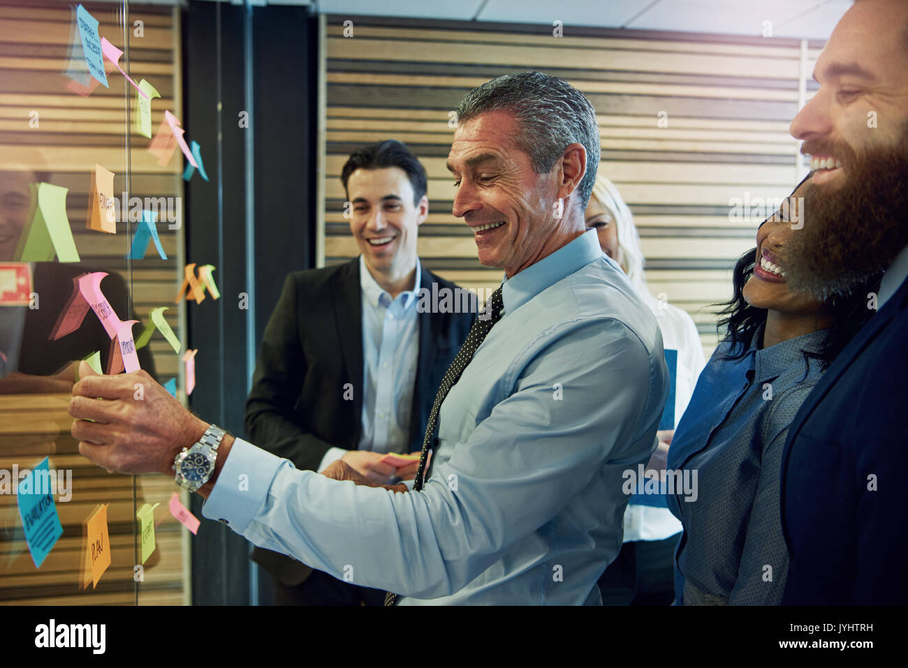 Side view of smiling businesspeople touching and looking at sticky notes on glass in office - Stock Image