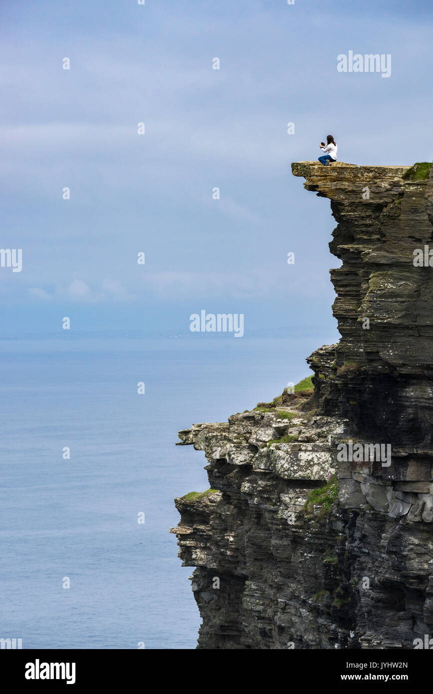 Woman on the edge of a cliff at Cliffs of Moher, Liscannor, Munster, Co.Clare, Ireland, Europe. - Stock Image