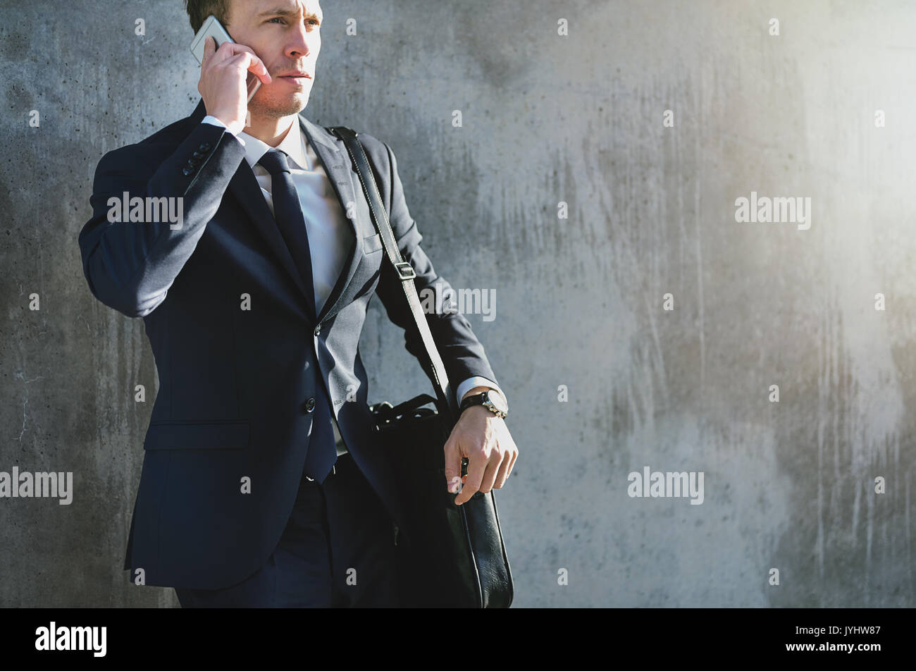 A confident businessman wearing the stylish formal suit and having a phone conversation. - Stock Image
