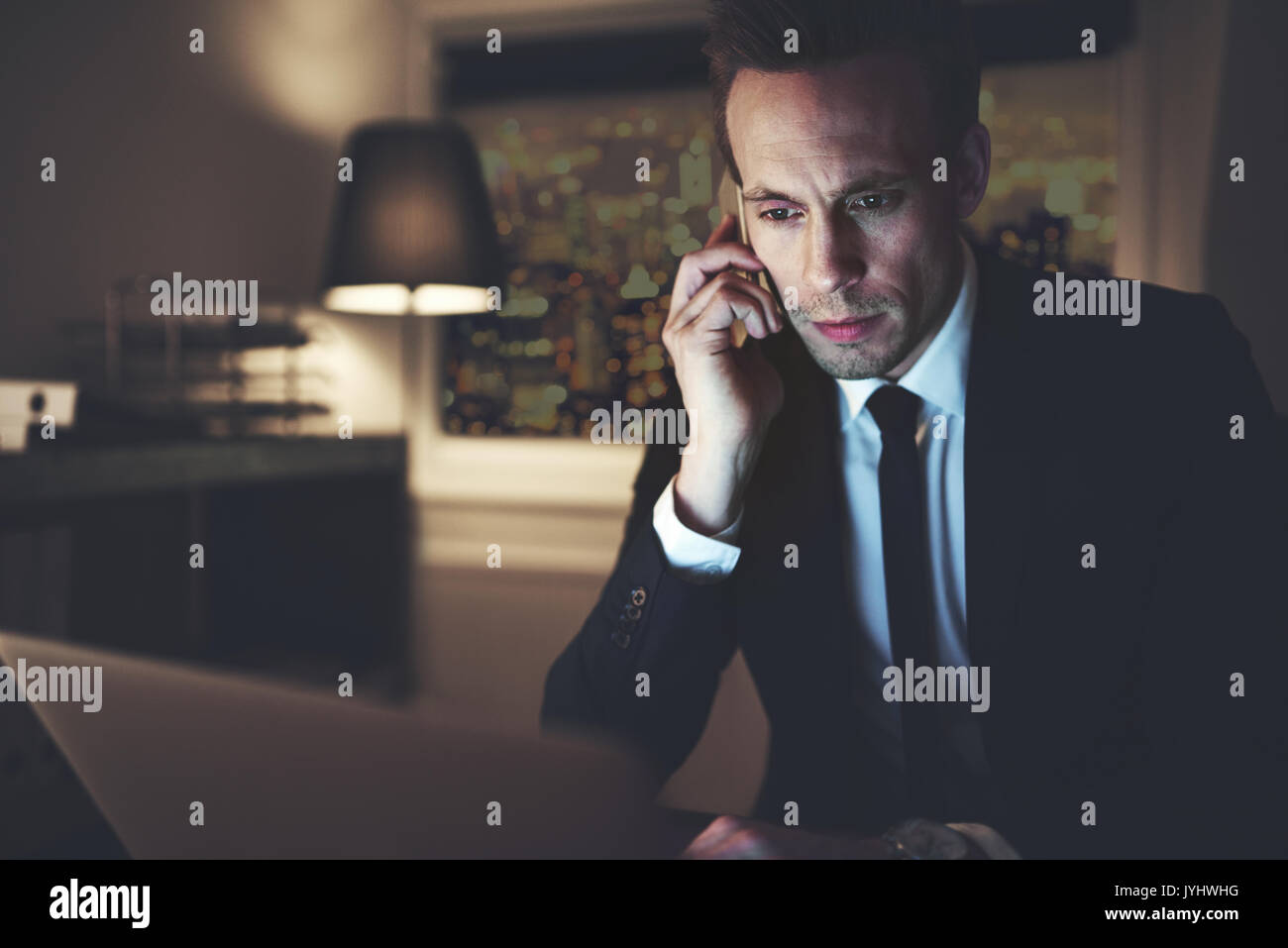 The office worker sitting at the laptop and talking the smartphonein the office at night. - Stock Image